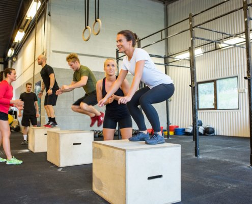 athletes jumping on boxes
